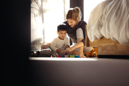 Mother and son playing with toys in bedroom