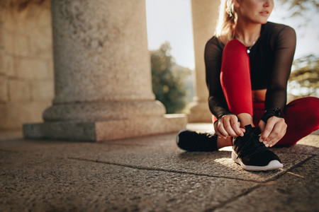 Fitness woman tying her shoe lace sitting on floor