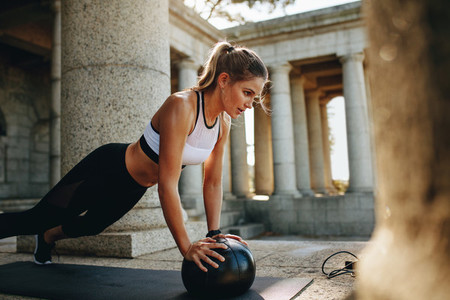 Fitness woman doing push ups using a medicine ball