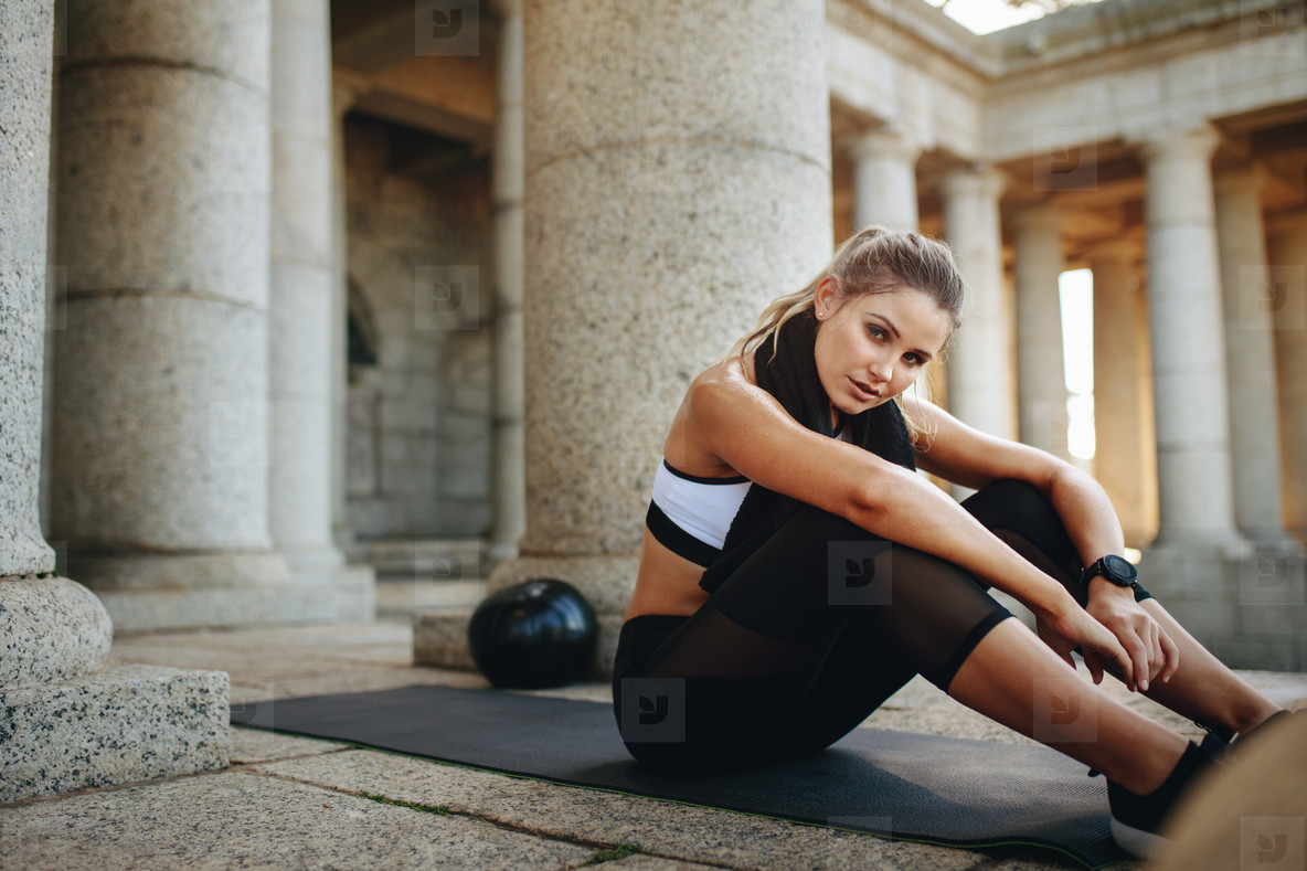 Female athlete taking a break from workout sitting on a training