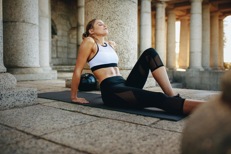 Fitness woman sitting on ground doing fitness exercises