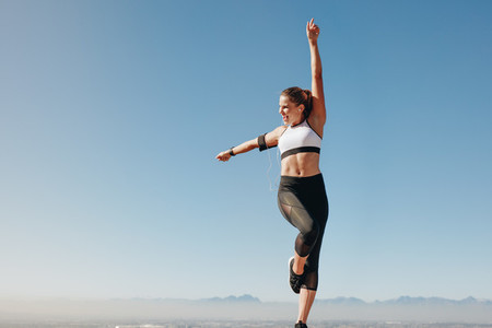 Female athlete standing on a hill and doing workout