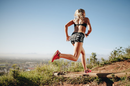 Fitness woman running on a hill