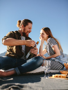 Couple on picnic at the beach opening a champagne bottle