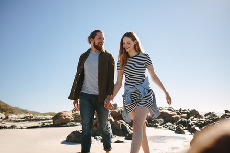 Beautiful couple strolling along a rocky beach