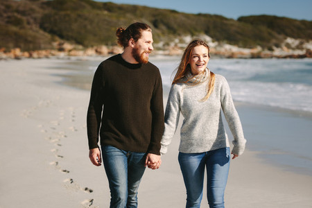 Smiling couple walking on beach