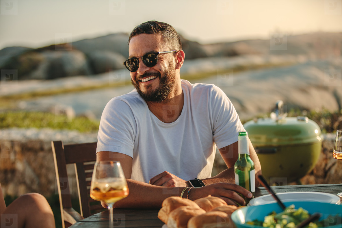 Man sitting outdoors with drinks and snacks