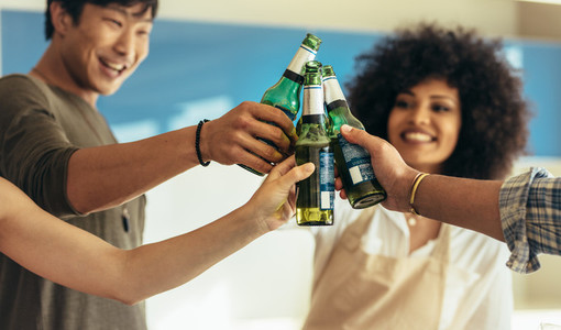 Friends having party toasting bottles of beer