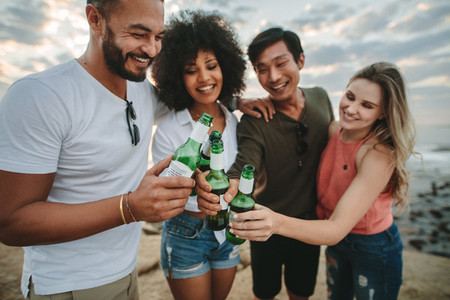 Group of friends having fun at the beach toasting beer