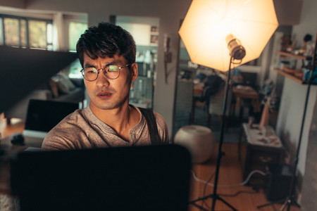Photographer adjusts studio lights before the shoot