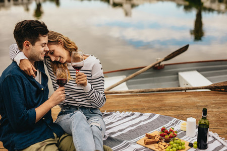 Couple on a date sitting together beside a lake drinking wine