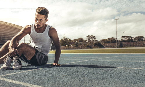 Runner sitting on running track holding his shoes