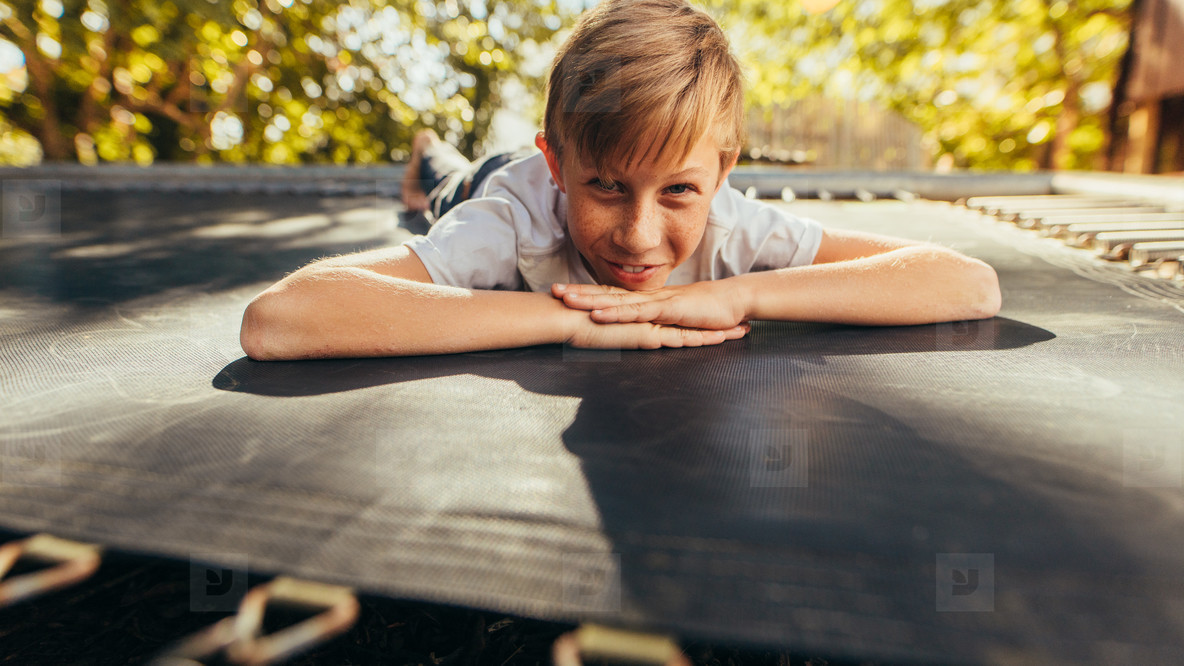 Small boy lying on trampoline outdoors