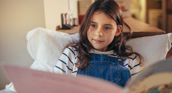 Girl at home reading a story book