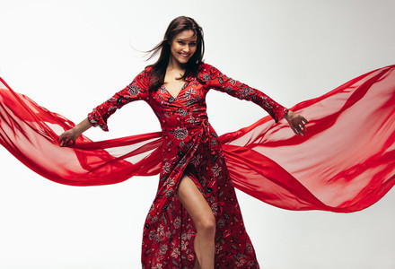 Beautiful woman in red dress with flying fabric