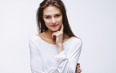 Attractive woman with finger on cheek