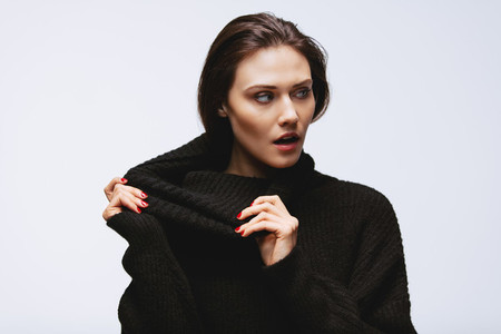 Woman pulling her turtleneck sweater