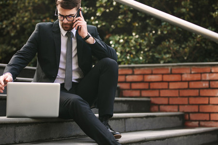 Businessman sitting on steps with laptop talking over phone