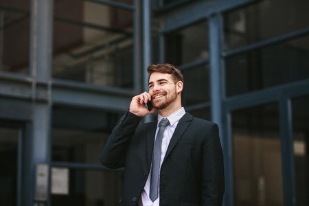 Businessman walking outdoors and talking on phone