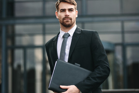 Businessman with a folder walking outdoors