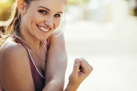 Smiling female athlete doing workout outdoors