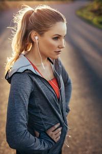 Portrait of a female runner standing on road