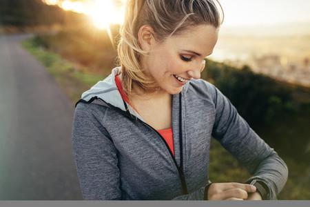 Female runner adjusting her wrist watch