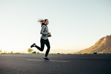 Woman athlete running on road