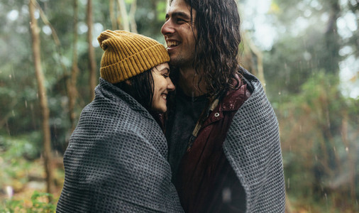 Couple in love standing under the rain wrapped in a blanket