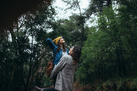 Young smiling couple enjoying rain in the forest