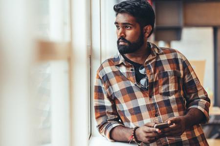 Man standing near a window looking outside