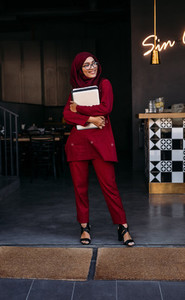 Muslim female standing at coffee shop door with laptop