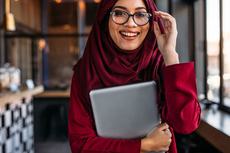 Woman in hijab at coffee shop with laptop
