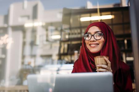 Beautiful muslim woman relaxing at cafe