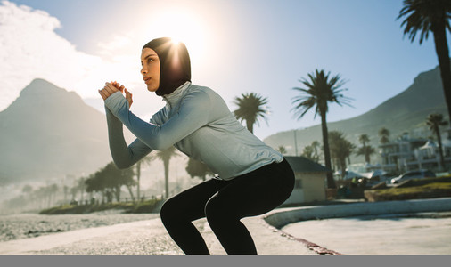 Fit woman doing squats outdoors in morning