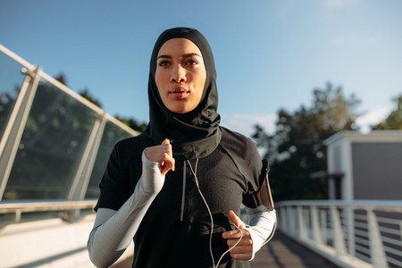 Healthy sporty woman in hijab jogging