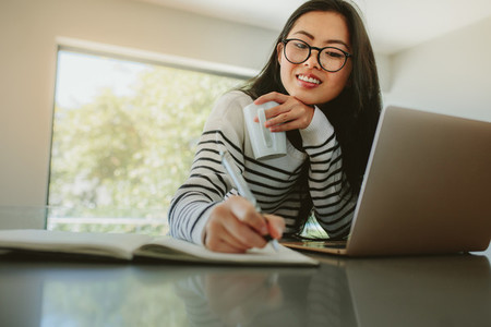 Woman studying at home with laptop on table