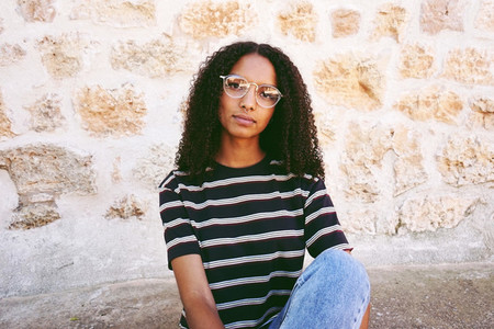 A portrait of serious young black woman wearing glasses  jeans a
