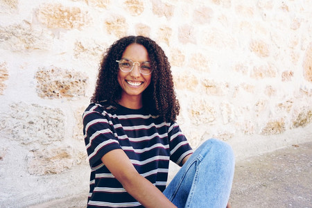 A portrait of happy smiling young black woman wearing glasses j