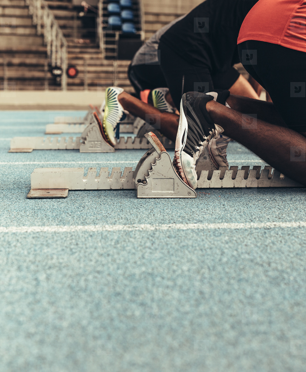 Athletes resting their feet on starting blocks on running track