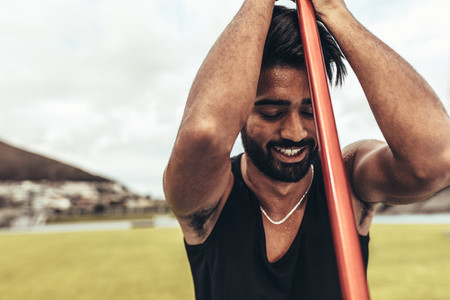 Tired athlete relaxing standing in the ground holding a javelin
