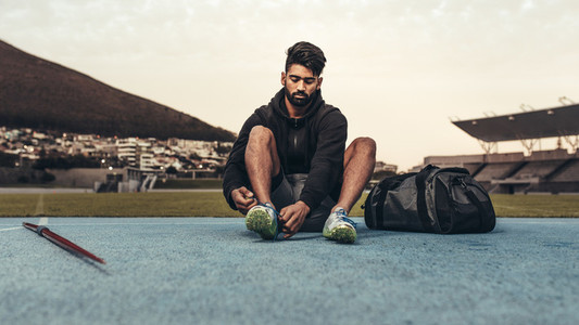 Athlete sitting on running track wearing his shoes