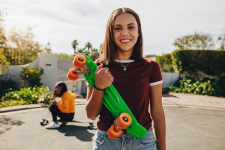 Smiling girl standing on street holding a skateboard