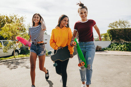 Girls walking in the street holding skateboards