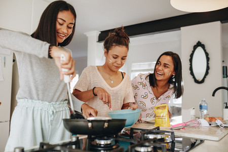 Three girls making food together standing in kitchen