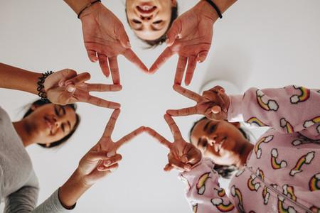 Girls making a star joining their fingers together