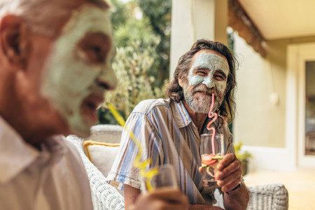 Retired friends with facial clay mask on drinking juice