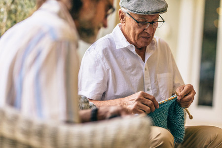 Two old men sitting knitting warm clothes