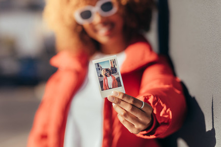 Portrait of a tourist woman holding a polaroid photo