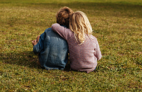 Siblings sitting on the grassy lawn